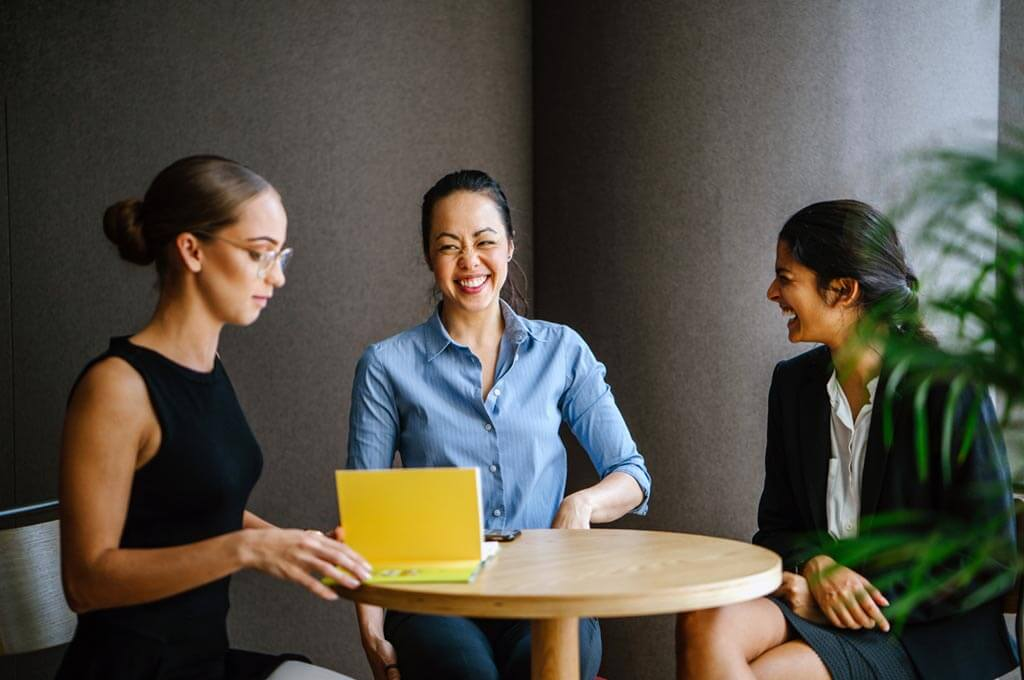professional women of varying ethnicities sit and have a meeting
